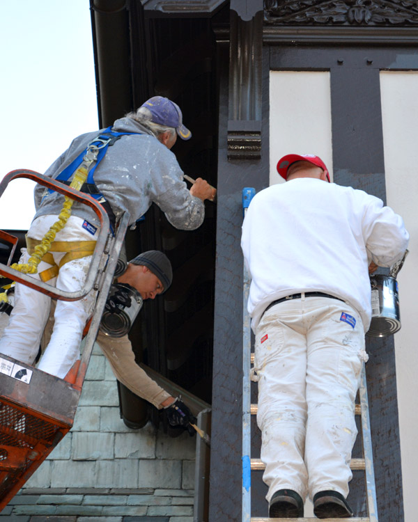 Three men painting exterior of home while on lift