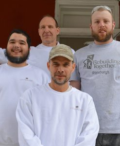 Photo of four male painters on front porch